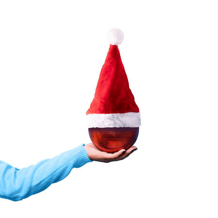 christmas red ball in santa claus hat on hand, isolated on white background, merry christmas concept