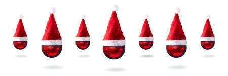 christmas red balls in santa claus hats over white background, merry christmas concept