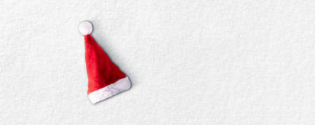 Christmas santa hat on white snow, panoramic image