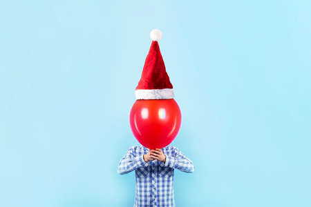 man holding red balloon in santa claus hat on a blue background, happy new year concept