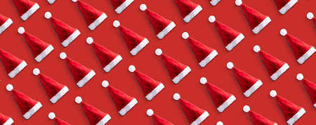 Creative Santa Claus hat pattern over red  background. Minimal winter flat lay Christmas concept, panoramic image