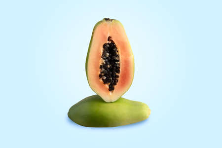 half sliced green papaya on blue background, diet concept