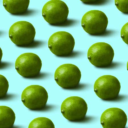 fresh, green limes pattern on blue background. Minimal flat lay food texture Zdjęcie Seryjne