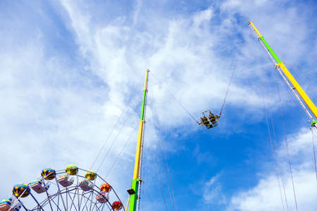 People riding high in the air on a dangerous carousel on blue sky background, summer holiday concept 写真素材