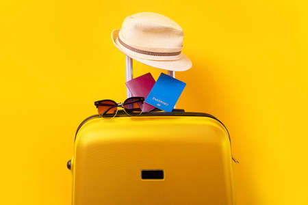 passports and sunglasses on yellow suitcase, concept of rest in hot countries, items for travel on a yellow background Zdjęcie Seryjne