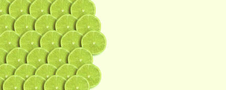 sliced green lime over yellow background, panoramic mock-up image, fresh fruit with space for text