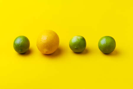 three limes and one lemon on a yellow background, concept of a unique, unusual idea 写真素材