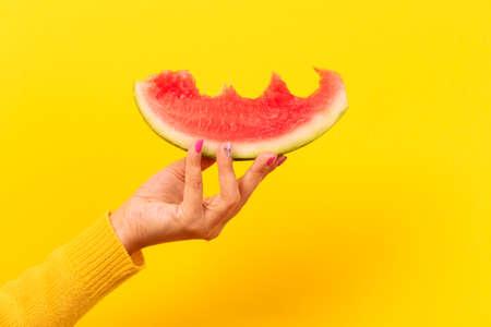bitten watermelon slice in hand over yellow background.  Summertime concept. 写真素材