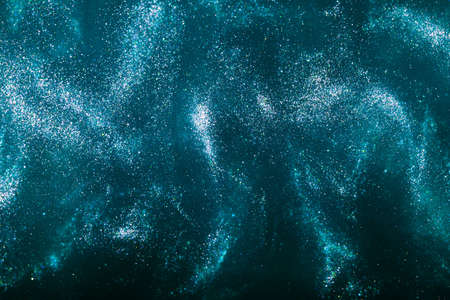 Abstract elegant, detailed blue glitter particles flow with shallow depth of field underwater. Holiday magic shimmering underwater space luxury background. Festive sparkles and lights