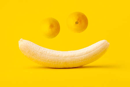 Peeled banana and two lemons on yellow background, funny smiling muzzle, summertime concept