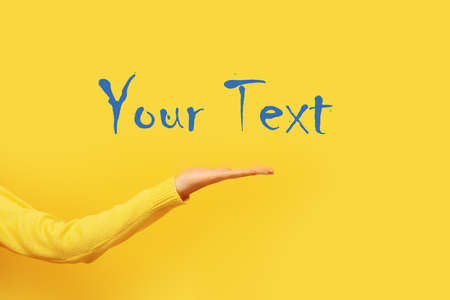 Palm presenting gesture over yellow background, female hand with space for text