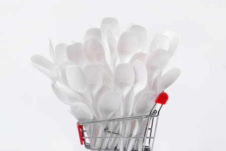 white plastic spoons in mini shopping cart on gray background 写真素材