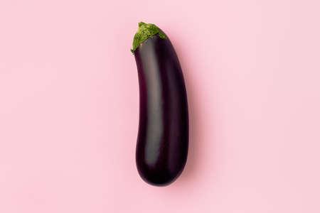 Fresh raw dark purple eggplant on pink background, the concept of vegetarianism