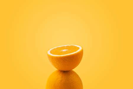half sliced orange balancing on one whole orange on colorful background