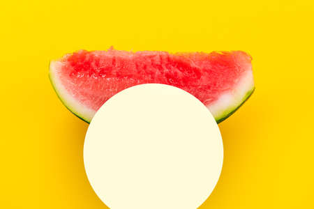 Watermelon slice over yellow background. Summertime concept. Mockup with space for text. 写真素材