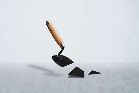 broken construction spatula over concrete room background