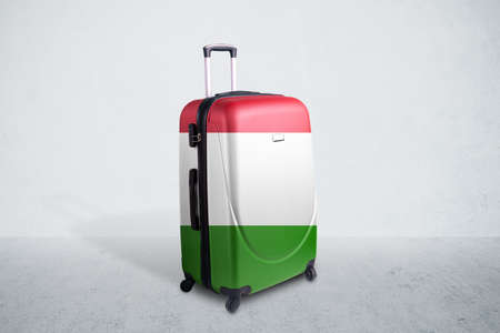 Travel suitcase with the flag of Italy. Holiday destination, suitcase over concrete room background 写真素材