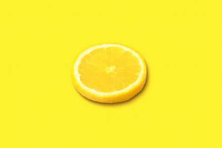 ripe lemon slice on yellow background, citrus fruit on bright