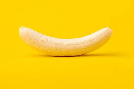 banana peeled on yellow background