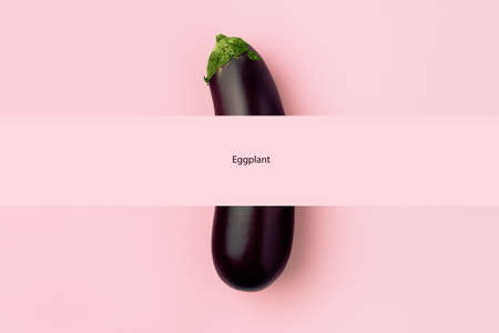Fresh raw dark purple eggplant on pink background with space for text, the concept of vegetarianism