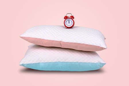 two modern pillows and red alarm clock on pink background, sleeping time concept