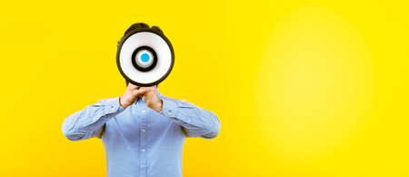 man with a megaphone over yellow background, panoramic image with space for text, announcement concept