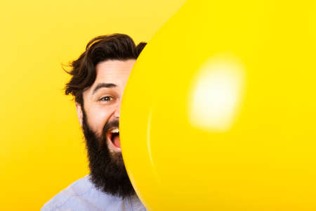 Handsome bearded man smiling and looking at camera while peeking out from above yellow balloon on yellow background, concept positive emotions, mock-up image with space for text Banco de Imagens