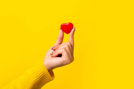 Hand holding a red heart over yellow background, heart health, and donation concepts