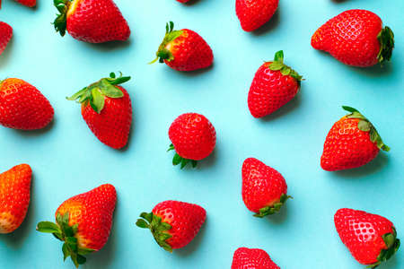Red strawberries on a blue background. Strawberry pattern
