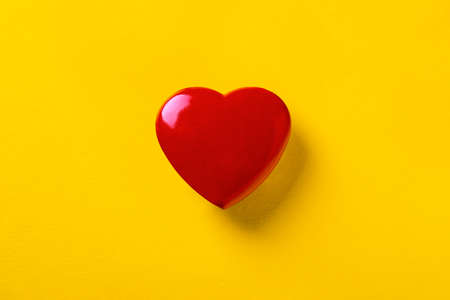 red heart on a yellow background, symbol of love, blank for Valentine's Day 免版税图像 - 140289333