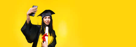 graduate woman makes selfie photo on phone over yellow background, concept of successful completion of studies, panoramic mock-up
