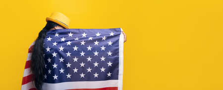 gir with American flag over yellow background, girl in fashionable hat with USA flag