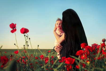 girl with a child in a poppy field, happy motherhood concept