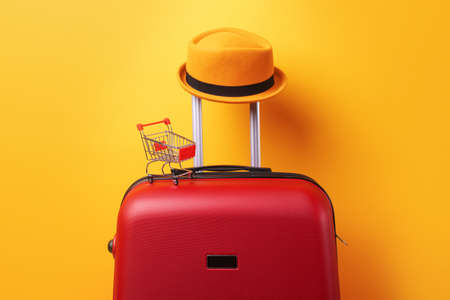 concept of shopping abroad, hat at suitcase with shopping cart over trend yellow background 免版税图像