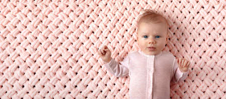 Beautiful newborn girl on a pink knitted plaid, panoramic mock-up image