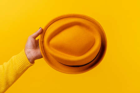 fashionable yellow felt hat in hand over yellow background