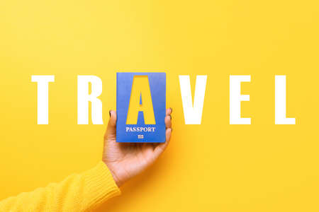 blue passport in hand over yellow background, world travel concept