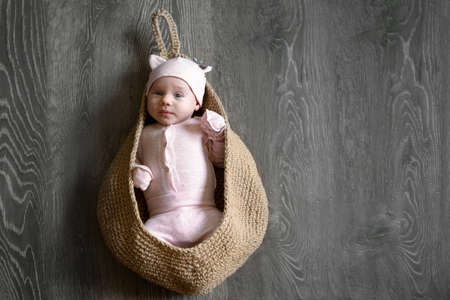 one month old baby in a knitted bag, mock-up image 免版税图像 - 152509208