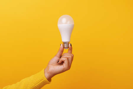 light bulb in hand over yellow background