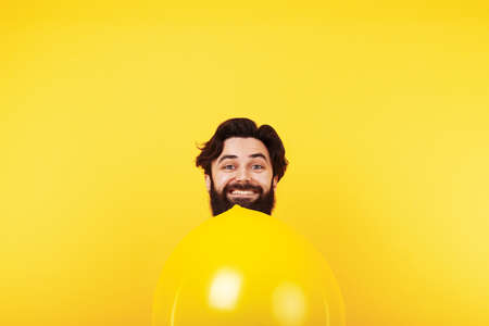 smiling man with inflatable yellow ball, holiday man on bright background