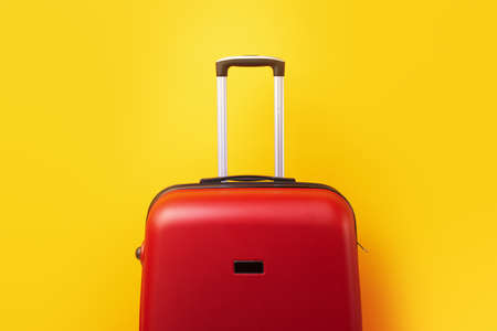 red travel suitcase close up over yellow background