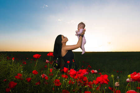 girl with a child in a poppy field on the sunset, happy motherhood concept
