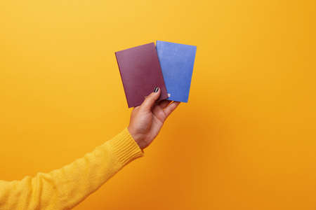 Hand holding two passports over yellow background 免版税图像