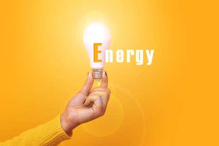 hand holding light bulb with inscription energy, illuminated light bulb, image over yellow background