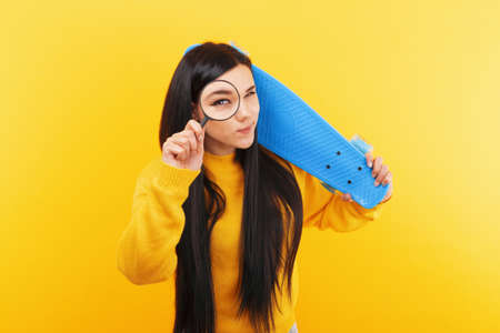 girl with skateboard and magnifier over yellow background, search for active youth recreation 免版税图像
