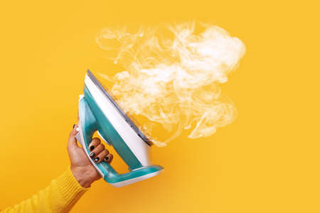 modern iron with steam in hand over yellow background 免版税图像