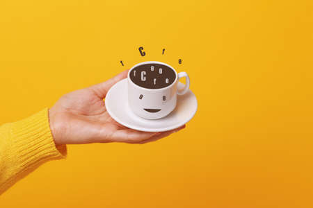 hand holding coffee cup over yellow background 免版税图像