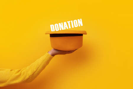 hat with donation inscription over yellow background, concept of generosity