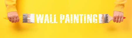Paint brush in hand over yellow background, wall painting concept, panoramic image 免版税图像