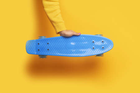 Hand holding skateboard over yellow background, youth entertainment